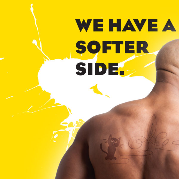 Pro-Ink Branding, back of head and shoulders of buff bald man with kitten tattoo and the words We have a softer side against a yellow background