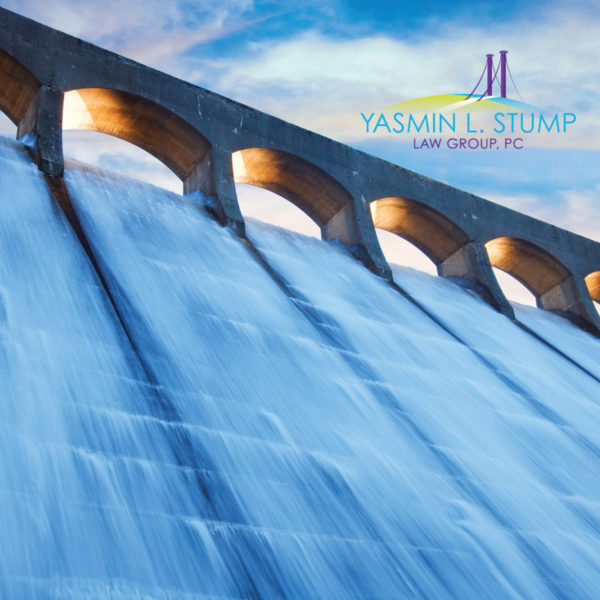 Yasmin L. Stump Law Branding Featured Image of water falling down the slope of a dam with logo in the sky